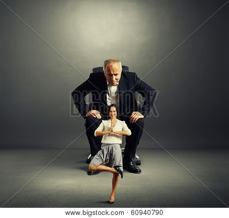 senior businessman sitting on the office chair and scrutinizing smiley businesswoman