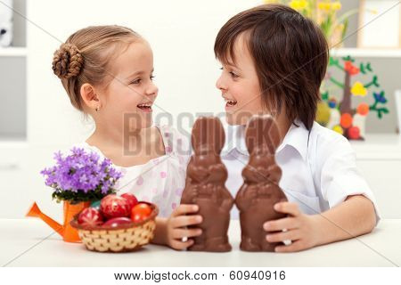 Happy kids at easter time laughing - with large chocolate bunnies and colorful eggs