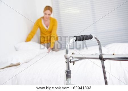 Cleaning lady doing housekeeping in nursing home with walker in front