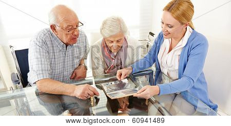 Senior citizens couple watching a photo album with their daughter