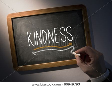 Hand writing the word kindness on black chalkboard