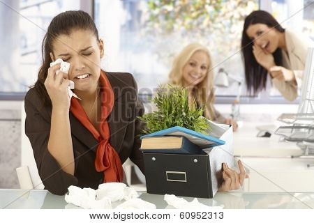 Fired young female office worker sitting at desk, crying, colleagues laughing at her at the background.