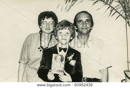 LODZ, POLAND, SEVENTIES - Vintage photo of little boy with his godparents at his First Communion