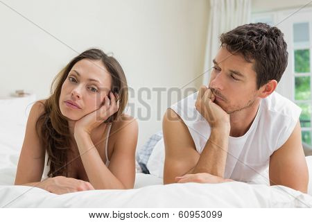 Unhappy couple not talking after an argument in bed at home