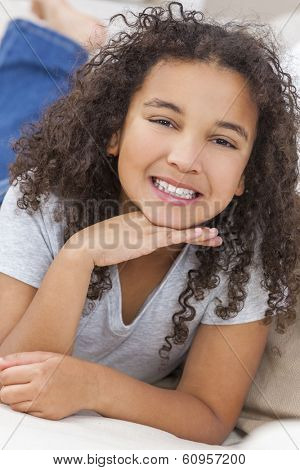 Beautiful young mixed race interracial African American girl child laying down smiling and showing off her perfect white teeth