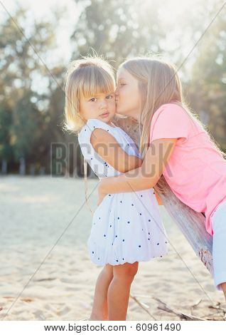 Adorable young sisters, little girls playing affectionately together at the beach