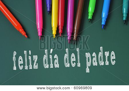 feliz dia del padre, happy fathers day written in spanish in a chalkboard, and some felt-tip pens of different colors poster