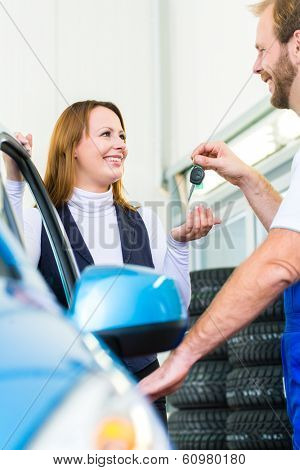Female client and mechanic in auto workshop or MOT with car for service inspection