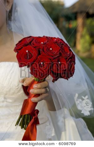 Bride holding a bouqet of red roses