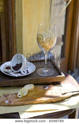 Coffee beans in a white cup and pasta in glasses. Table near caffe