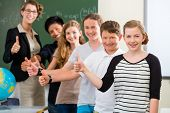 School class teacher and students stand in front of a blackboard with math work in a classroom during lesson poster