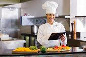 Portrait of a smiling young female chef using digital tablet while cutting vegetables in the kitchen poster