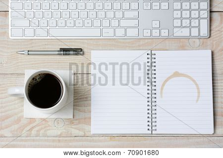 High angle shot of a white rustic desk with a modern keyboard, coffee cup and notebook with a coffee stain. Horizontal format.