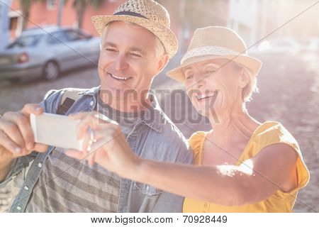 Happy mature couple taking a selfie together in the city on a sunny day