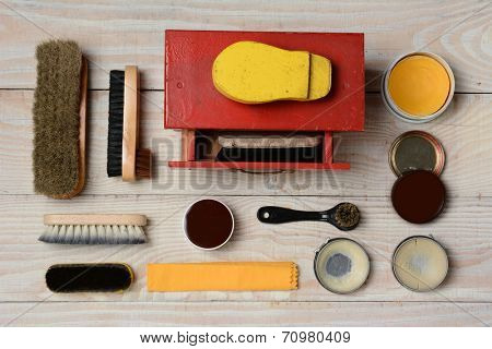 High angle view of  an antique shoe shine kit and its accessories, including brushes, polish, and buffing cloth. Horizontal format on a white wood surface.