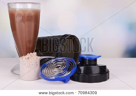 Whey protein powder with shake and plastic shaker on table on bright background