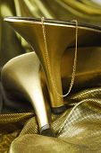close up of woman shoes and golden jewelry on golden fabric poster