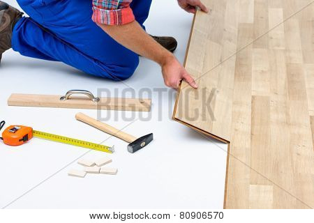 carpenter worker installing laminate flooring in the room poster