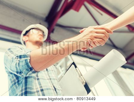 architecture and home renovation concept - builder with blueprint shaking partner hand poster
