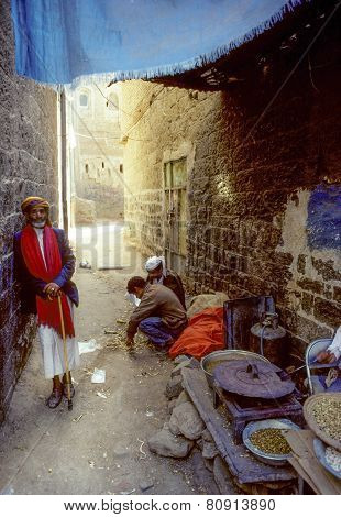 Old Man In A Narrow Road With A Foodstall Selling Roasted Nut