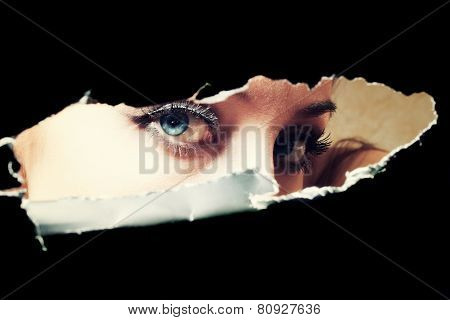Blue Eyes Of Young Woman Peeping Through A Hole