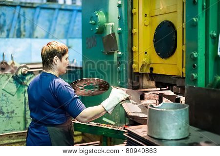 Woman stamps details on hydraulic press