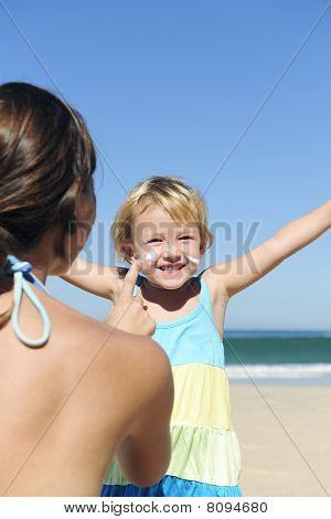 Mother Applying Suncream To Her Happy Child