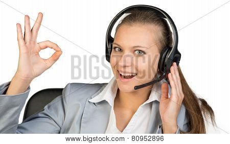 Businesswoman in headset making okay gesture, her other hand on headset speaker, looking at camera, laughing. Isolated over white background poster
