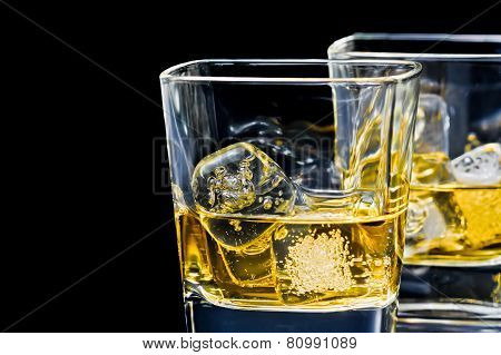 Two Glasses Of Alcoholic Drink With Ice On Black Background