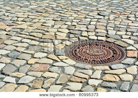 Manhole cover and cobblestones