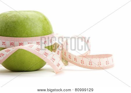 A green apple and a measurement tape