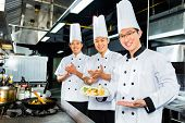 Asian Indonesian chefs along with other cooks in restaurant or hotel kitchen cooking or fry with a pan at the stove poster