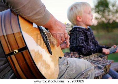 Father And Son Outside Playing Guitar And Singing