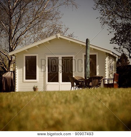 Beautiful luxury wooden Summerhouse in a country garden with tables chairs sun umbrella trees blue sky and green grass. The Summer house is a romantic and relaxing garden retreat. Nostalgic sepia instagram effect poster