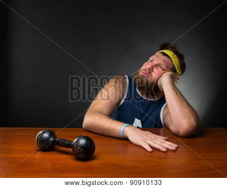 Dreaming man and a dumbbell