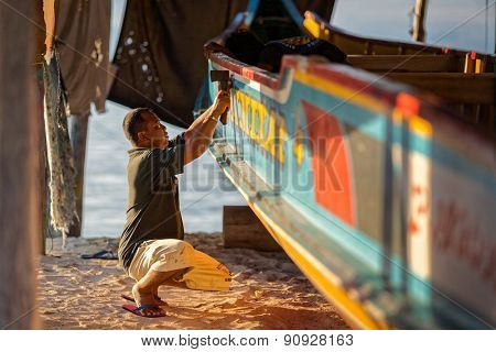 SABAH, MALAYSIA - JUNE 28, 2008: An unidentified boat maker makes the final touches to a fishing boat he had made in his factory. Boats are a major form  of transportation on this island.