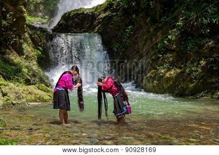 LONGJI, CHINA - MAY 24, 2010: Unidentified women wash their hair at a stream in the village. Red Yao ethnic minority women here regard keeping long hair as a sign of beauty..