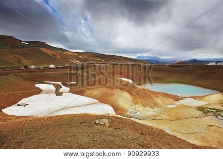 July in Iceland. Krafla lake in the crater of an extinct volcano. On the banks are last year's snow fields poster