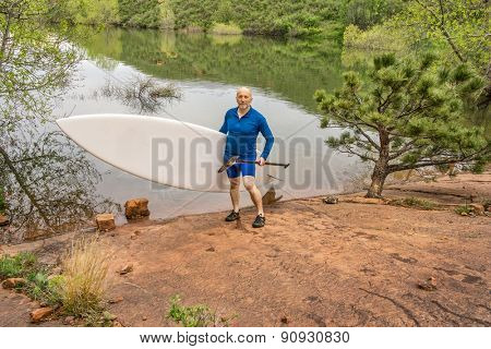 senior paddler carrying paddleboard and paddle on a rocky shore of a lake - Horsetooth Reservoir, Fort Collins, Colorado