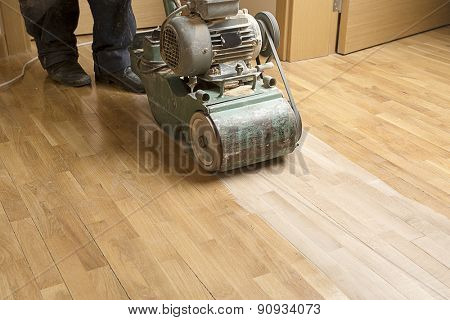 Wood floor polishing maintenance work by grinding machine.