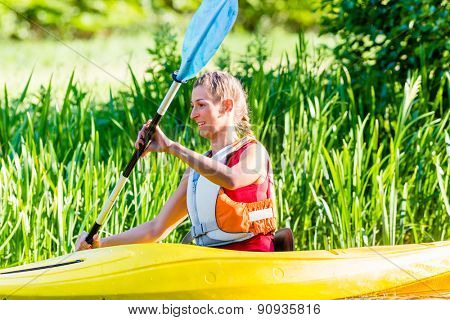 Woman paddling with canoe on forest river
