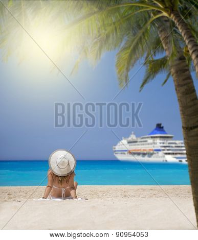 Woman relaxing on the  beach watching a cruiseship passing by