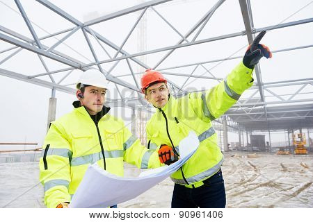 engineers construction foreman managers outdoors indoors at building site with blueprints