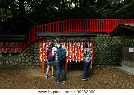 Kyoto, Japan - May 4, 2015: People hang wishes and make offerings made of small wooden planks on a fox ema at Fushimi Inari shrine at Kyoto