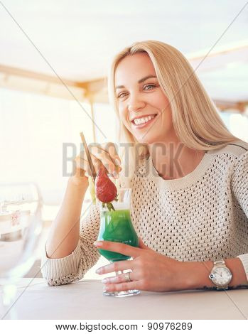 Smiling Blonde Woman With Cooling Cocktail In Sunny Cafe