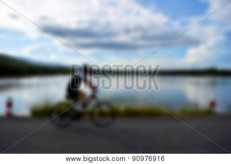 Cyclists On the road along the lake ,soft blur focus