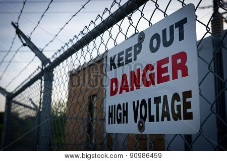 Danger Keep Out High Voltage Sign On Barbed Wire Fence