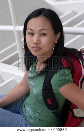 Asian Student With Backpack Sitting On Steps