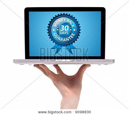 A Male Hand Holding A Laptop With Money Back 30 Days Label