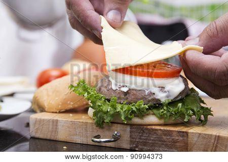 Close Up Chef Putting Slice Of Cheese On The Hamburger Bun